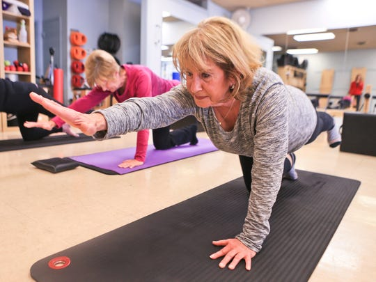Phyllis Green, 70, works balancing her body on one knee while participating in a Buff Bones class at Pilates Village in St. Matthews.