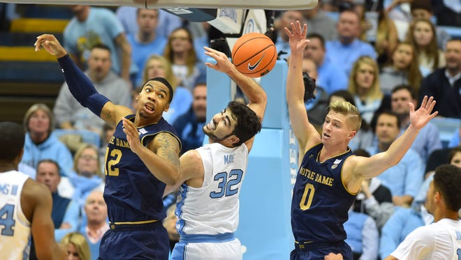Notre Dame Fighting Irish forward Elijah Burns (12) and guard Rex Pflueger (0) fight for the ball with North Carolina Tar Heels forward Luke Maye (32) in the first half at Dean E. Smith Center.