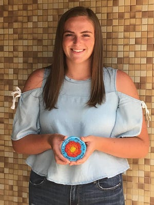 Chelsey Catton shows off the medallion she created that will be sought by searchers in the 2020 Pekin Marigold Festival Medallion Hunt.