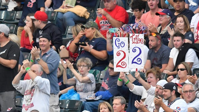 A fan holds a sign hoping the Indians win 22 games in a row.