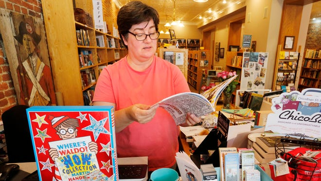 """Owner Tamzin Malone flips through a Where's Waldo coloring book Monday, July 10, 2017, at Main Street Books, 426 Main Street in downtown Lafayette. Main Street Books has launched a shop local """"Where's Waldo"""" campaign in which contestants can look for Waldo in a scavenger hunt at local businesses. A variety of Where's Waldo books, including the coloring book, are available as prizes."""