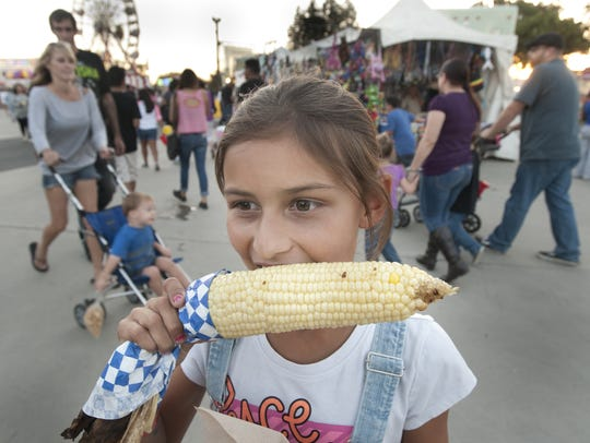 Vanessa Light, 9, of Tulare, chomps an ear of corn