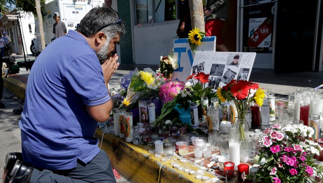Jose Cardoso pays his respects at a makeshift memorial in front of the IV Deli Mart, where part of Friday night's mass shooting took place by a drive-by shooter Sunday, May 25, 2014, in the Isla Vista area near Goleta, Calif. Sheriff's officials said Elliot Rodger, 22, went on a rampage near the University of California, Santa Barbara, stabbing three people to death at his apartment before shooting and killing three more in a crime spree through a nearby neighborhood.