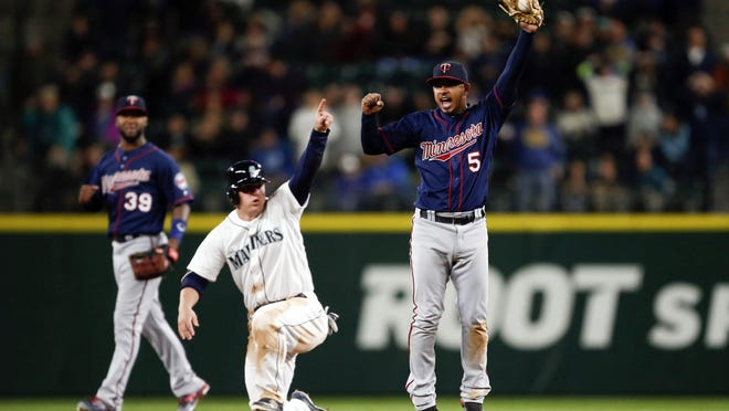 Minnesota Twins shortstop Eduardo Escobar (5) celebrates tagging out Seattle Mariners third baseman Kyle Seager (15) at second base for the game-ending double play during the ninth inning early Sunday morning at Safeco Field. The Twins won 6-5.