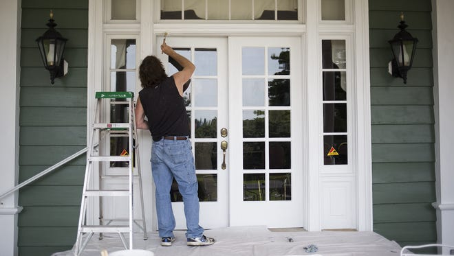 Painter Eric Stambaugh works on the Grandview Golf Club's clubhouse in Dover Township as workers transform the exterior in preparation for the opening of a second Brewvino location.