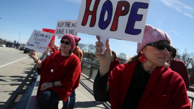 Linda Nielsen, left, and Lillie Minsart, right, march and hold signs Wednesday as they and around 100 others marched for International Women's Day.