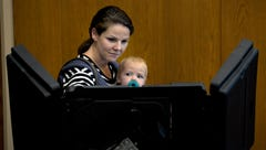 Kate Watkins votes as her daughter Lillian, 1, looks