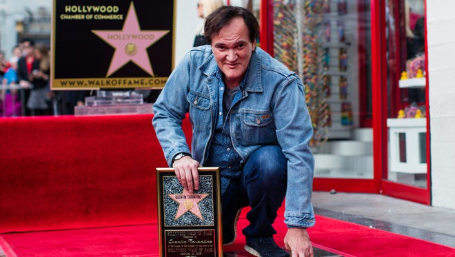 Filmmaker Quentin Tarantino poses with his star on the Hollywood Walk of Fame on Dec.21, 2015 in Hollywood.