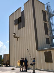 "Tech. Sgt. Ben Domian, a survival, evasion, resistance, and escape specialist with the 920th Rescue Wing, repels down a training tower in front of a Fox TV camera crew June 15, 2016 at Patrick Air Force Base, Fla. The network shot footage of Domian to use for its newest reality show, ""Kicking and Screaming,"" which airs March. 9. Domian is one of 20 contestants on the show."