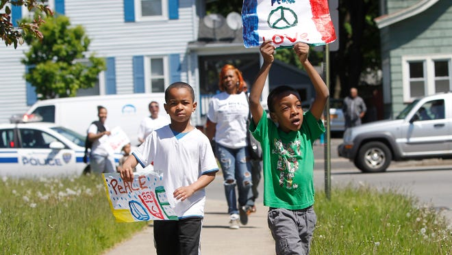 Geveon Booker, left, and Kamarion Steward, both 7 and of Rochester, take part in Saturday's walk through the Beechwood neighborhood to call for an end to violence.