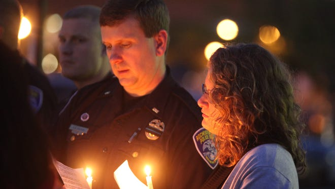 Rochester police Lt. Korey Brown and his wife, Elena Brown, sing hymns Friday during the Partners Behind the Lines-sponsored vigil at the Public Safety Building.