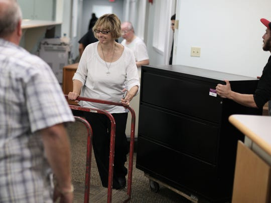 Sister Janice Brown from Fraser moves a cart out of the way as movers bring in furniture from the previous location on Friday, Sept. 26, 2014, at the Dominican Literacy Center in Detroit.