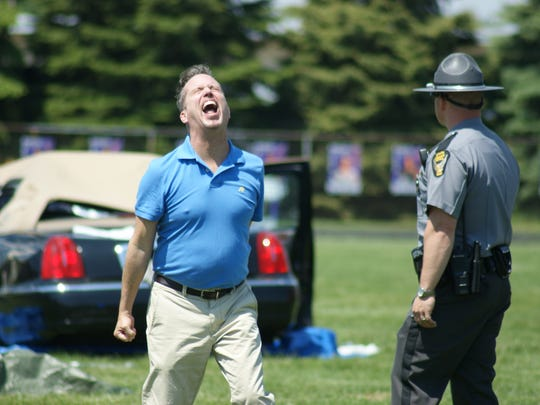Fremont attorney Chris Fiegl plays a parent of a student in a mock crash who was just told that his son was dead.