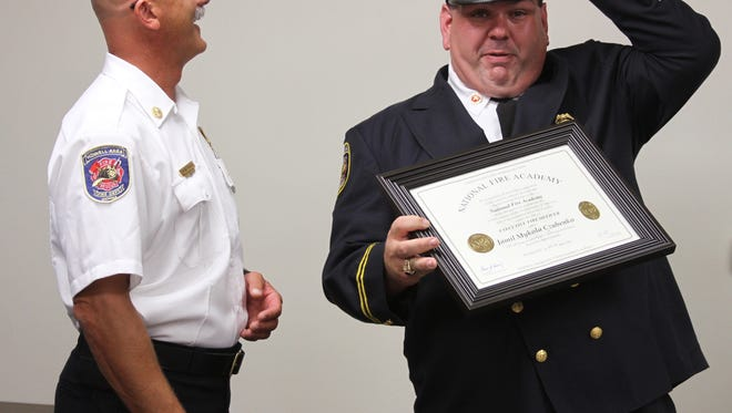Battalion Chief Jamil Czubenko, right, places his fire cap on his head as he received recognition Wednesday for successfully completing the National Fire Academy's Executive Fire Officer program. Chief Andy Pless, left, presented the award to Czubenko, who is also the department's fire marshal, on behalf of the U.S. Fire Administration at the fire board's meeting at the Oceola Township Hall.
