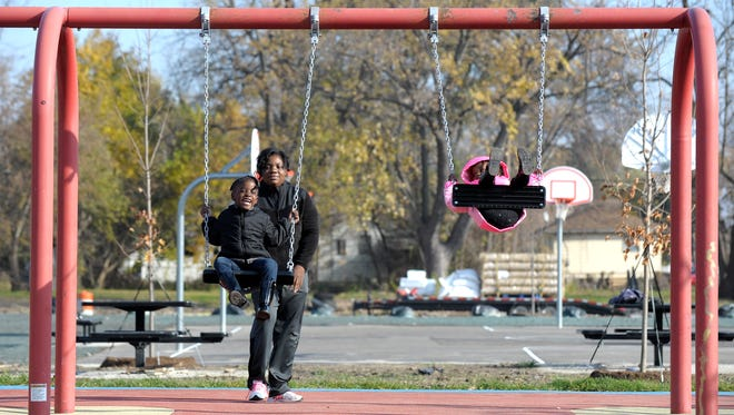 """This is the """"after"""" condition of Mansfield-Diversey Park. Janea Fletcher, 28, pushes her daughter, Amour, 4, as sister and daughter, Rose, 2, all of Detroit, watches at a park under renovation at Mansfield-Diversey Park on Detroit's NW side, Thursday, November 17, 2016."""