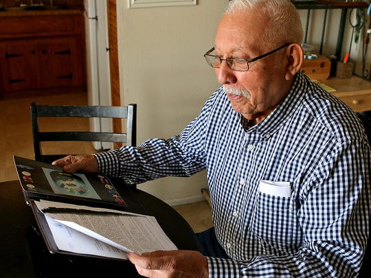 Roger Herrera looks over the military records of his oldest brother, Raul, in his home Wednesday afternoon.