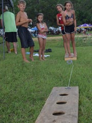 LEFT: Slay Coleman (left) Reesi Coleman, Rylee Coleman and Laynee Coleman play ring toss at Indian Creek Recreation Area in Woodworth on Saturday.