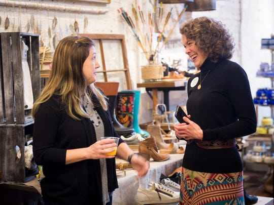 Carrie McConkey, right, speaks with a guest at a networking event held at Tori Mason Shoes in Market Square on Wednesday, March 22, 2017. McConkey, owner of Carrie M. Fashion Consulting, hosts networking events in local stores to promote brick and mortar shopping.