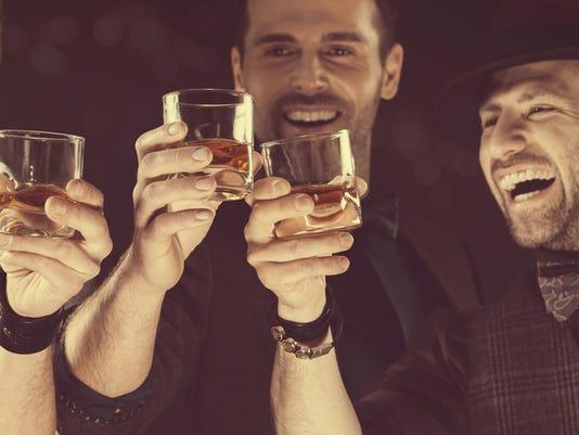 Happy elegant men toasting with whiskey