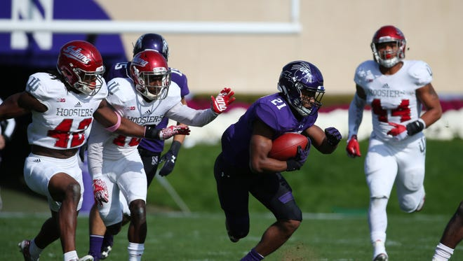 Northwestern Wildcats running back Justin Jackson (21) runs past Indiana Hoosiers defensive back Marcelino Ball (42) in the first quarter at Ryan Field.