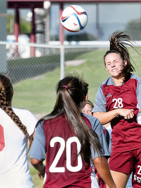 Gary Mook/For the Las Cruces Sun-News   New Mexico State's Sarina Stockton goes above the crowd for the ball during the second half of play Wednesday night at the NMSU Soccer Complex against New Mexico.