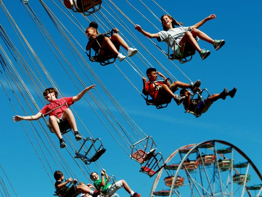 Abby Battle, top right, 12, holds out her arms as she soars on the Wave Swinger during the final day of the annual Delta Fair and Music Festival at the Agricenter Sept. 13, 2015.