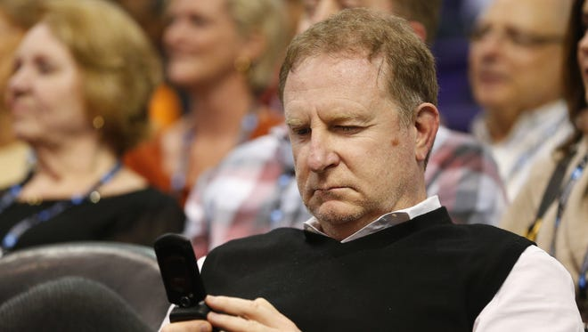 Phoenix Suns owner Robert Sarver uses a flipphone while watching his team play against the New Orleans Pelicans during the first quarter at Talking Stick Resort Arena Feb. 13, 2017.