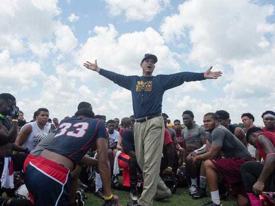 Harbaugh speaks to participants during a satellite