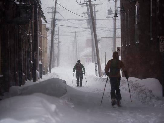 A pair of skiers make their way down an alley in downtown