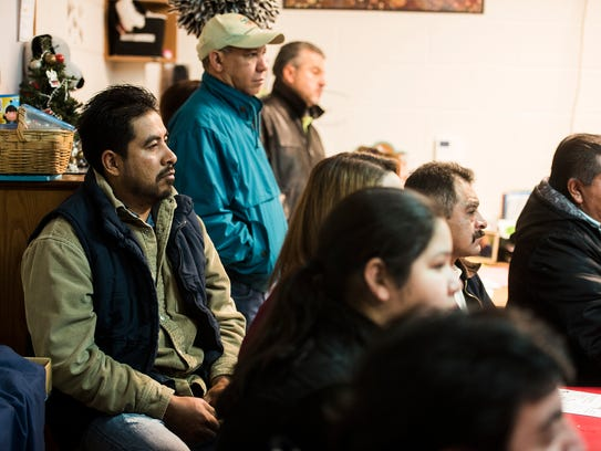 Members of the Hispanic community of Adams County listen