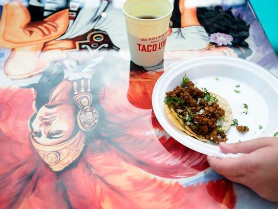 A person prepares to eat a taco during the Taco Libre