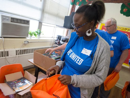Alicia Taylor, a United Way volunteer, puts books into