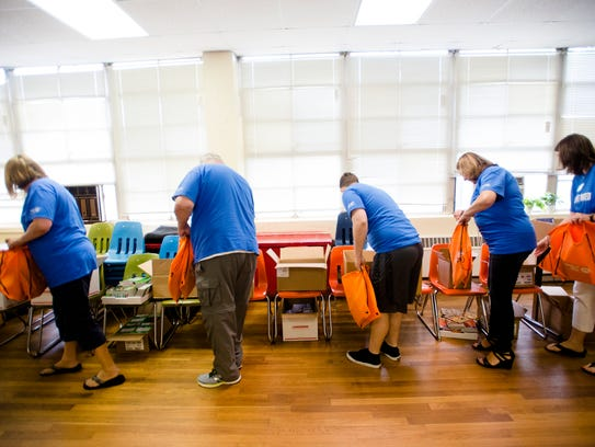 United Way volunteers put books into book bags for