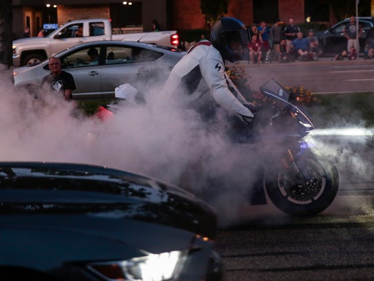 A motorcyclist does a burnout as he cruises down Woodward