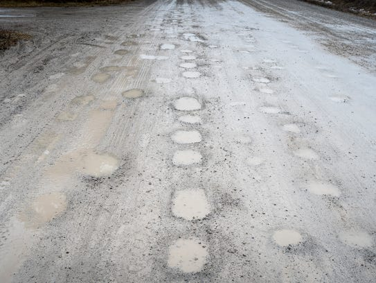 Potholes along Palms Road in Columbus fill with rain