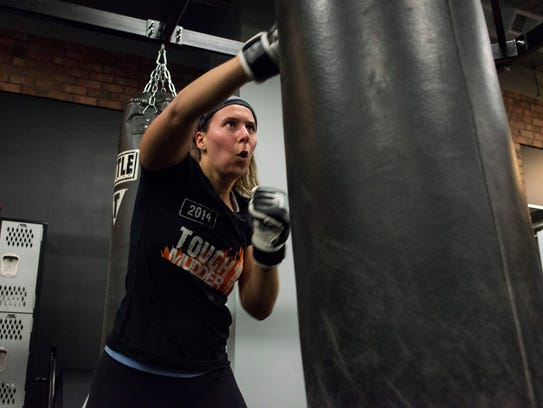 Alex Turner, 28, of Ann Arbor, works on her punches during her evening class at the Title Boxing Club.