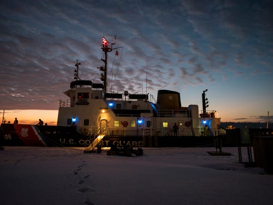 The sun rises behind the USCGC Neah Bay before launching