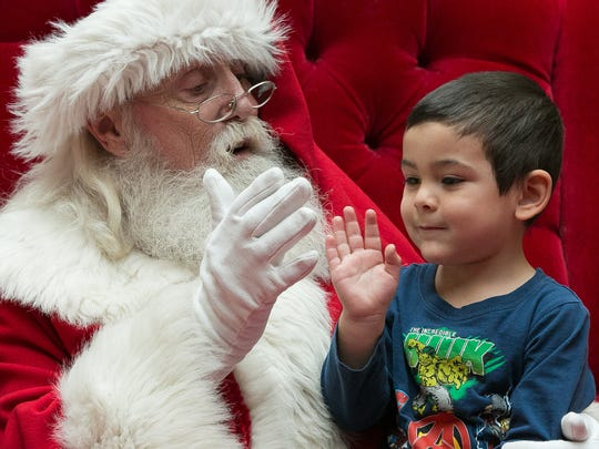 Ayden Padilla, 3, gets a high five from Santa while