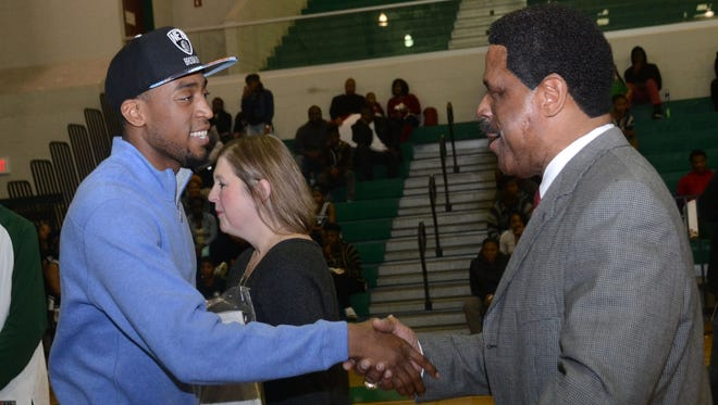 Former Peabody star and current NBA player Markel Brown (left) shakes hands with his former coach Charles Smith during a ceremony held in 2015 at Peabody Magnet High School where Brown's jersey was retired. Smith has seen over 60 players receive college scholarships.