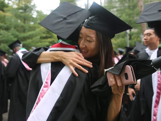 Friends Kristin Diep, right, and Austin Atsango hug each other before Vassar College's commencement ceremony last spring.