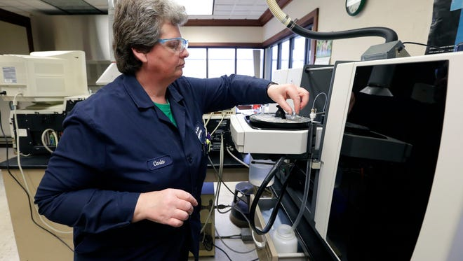 Metals analyst Carla Brown uses an atomic absorption spectrometer to analyze drinking water for lead Thursday at Badger Laboratories & Engineering Inc., in Neenah. Green Bay is testing samples of water from 100 homes for lead levels.
