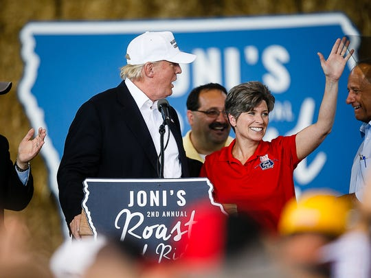 Republican presidential candidate Donald Trump is accompanied by Sen. Joni Ernst during her Roast and Ride event at the Iowa State Fairgrounds on Saturday, Aug. 27, 2016 in Des Moines.