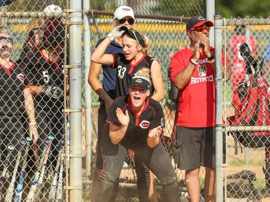 The Cincinnati Reds RBI softball team gets excited ion the bench during their RBI World Series trip.