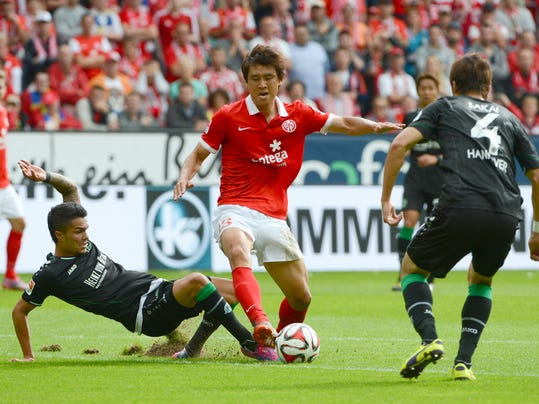 Mainz' Koo Ja-cheol, center,  challenges for the ball with Hannover's Leonardo Bittencourt, left, and  Hiroki Sakai  during the German Bundesliga soccer match between FSV Mainz 05 and Hannover 96 in Mainz, Germanyy, Sunday Aug. 31, 2014.  (AP Photo/dpa, Arne Dedert)