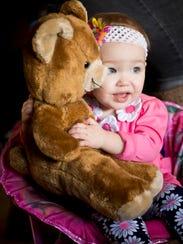 Eva Frank hugs a favorite plush toy bear at her grandmother's