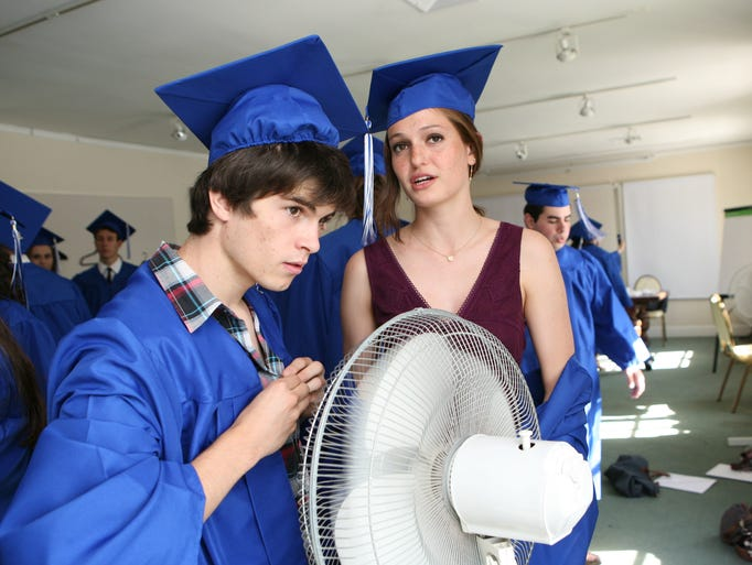 Sebastien LeCoz and Claire Charriaud cool off with a fan as the French American School of New York celebrates their 2014 graduation at the Wainwright House in Rye, June 15, 2014.