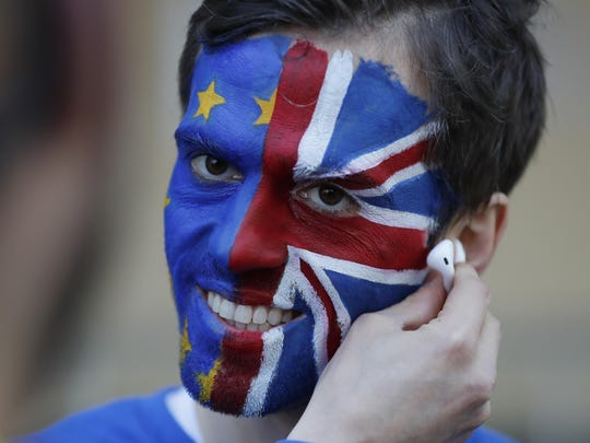An activist poses with his face painted in the EU and Union Flag colors during an anti-Brexit campaign stunt outside EU headquarters during an EU summit in Brussels, Thursday, March 21, 2019.