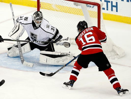 New Jersey Devils center Jacob Josefson (16), of Sweden, attacks on the net of Los Angeles Kings goalie Peter Budaj (31), of Slovakia, during the third period of an NHL hockey game, Tuesday, Jan. 24, 2017, in Newark, N.J. (AP Photo/Julio Cortez)