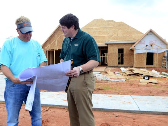 Jeff Lacher, right, speaks with contractor David Harvey
