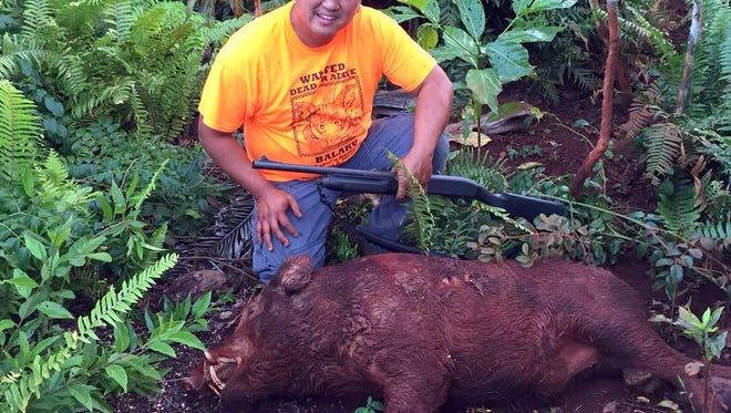 In this December 2015 file photo, courtesy of the Department of Agriculture,  John Jocson poses next to the boar that he caught when competing at the 5th annual Guam Pig Hunting Derby.
